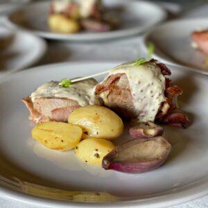 Maialino al punto rosa con salsa alla senape antica, patatine al forno e scalogni dorati